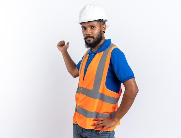 Selbstbewusster junger baumeister in uniform mit schutzhelm, der nach hinten zeigt, isoliert auf weißer wand mit kopierraum
