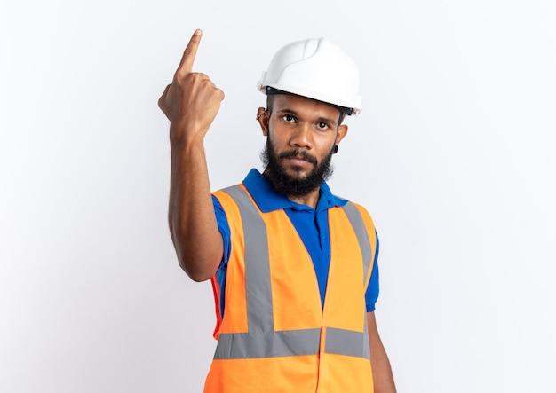 Selbstbewusster junger baumeister in uniform mit schutzhelm, der nach vorne zeigt, isoliert auf weißer wand mit kopierraum