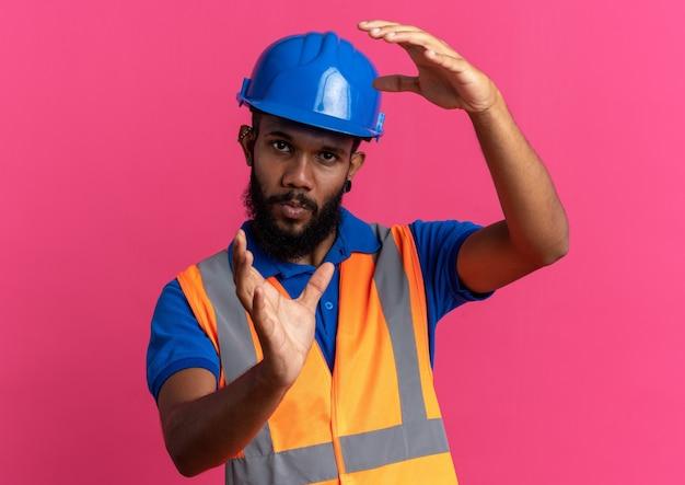 Selbstbewusster junger baumeister in uniform mit schutzhelm, der vorgibt, etwas isoliert auf rosa wand mit kopienraum zu halten