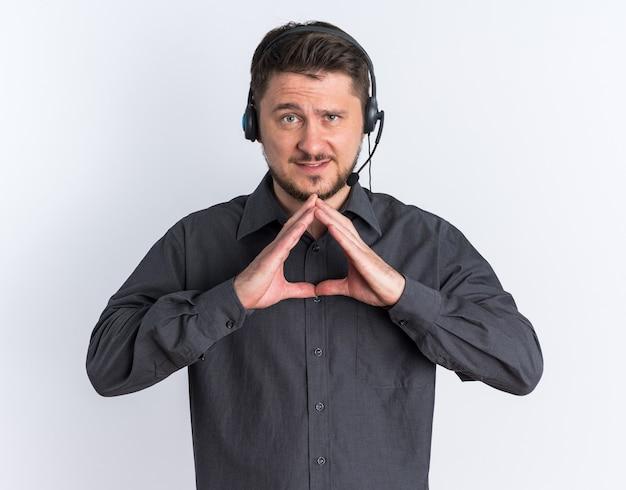 Selbstbewusster junger blonder gutaussehender mann mit headset zeigt ein dreieck, das vorne isoliert auf weißer wand schaut