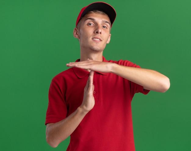 Selbstbewusster junger blonder lieferjunge gestikuliert auszeit handzeichen