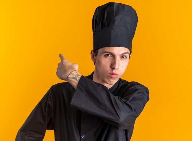 Selbstbewusster junger blonder männlicher koch in kochuniform und mütze mit blick auf die kamera, die hinter isoliert auf orangefarbener wand zeigt