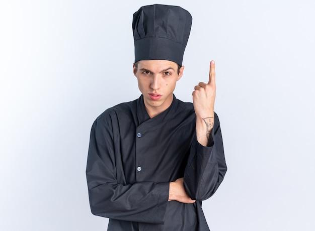 Selbstbewusster junger blonder männlicher koch in kochuniform und mütze mit blick auf die kamera mit blick auf die kamera, die nach oben zeigt, isoliert auf weißer wand mit kopierraum