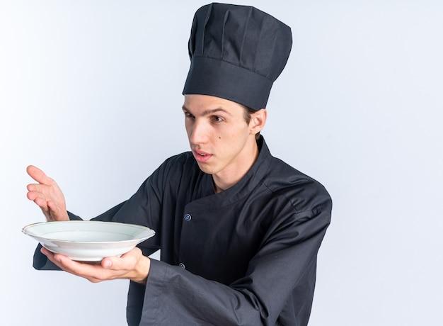 Selbstbewusster junger blonder männlicher koch in kochuniform und mütze mit blick auf die seite, die den teller mit der hand ausstreckt