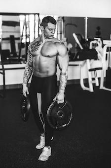 Selbstbewusster junger bodybuilder, der in einem modernen fitnessstudio steht.