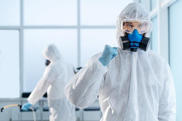 Selbstbewusster junger desinfektor steht in einem infizierten raum