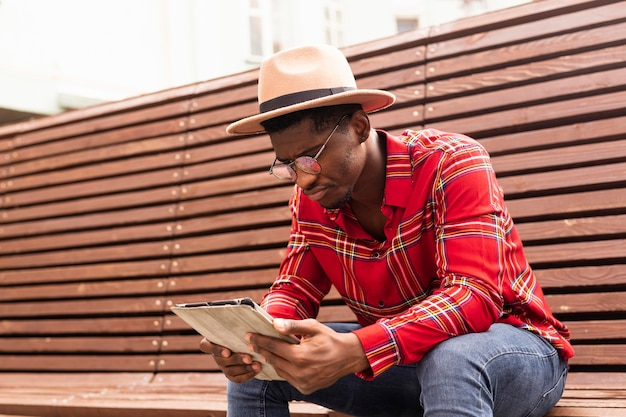 Selbstbewusster junger erwachsener im roten hemd, das eine tafel betrachtet