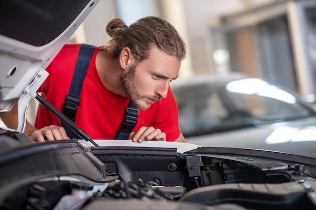 Selbstbewusster junger erwachsener mann in der arbeitsuniform, die an autos arbeitet