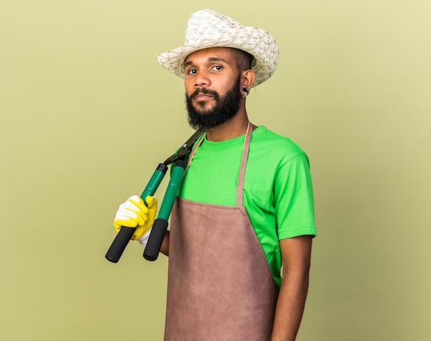 Selbstbewusster junger gärtner, der einen gartenhut mit handschuhen trägt, der schermaschinen auf der schulter hält