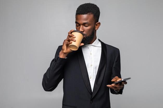 Selbstbewusster junger geschäftsmann, der eine stehende jacke trägt, die das mobiltelefon benutzt und eine tasse kaffee zum mitnehmen hält