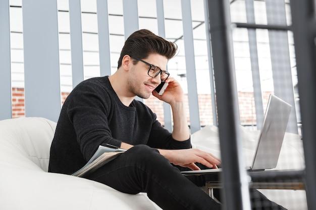 Selbstbewusster junger geschäftsmann, der im büro arbeitet, während er in einer couch sitzt und auf handy spricht