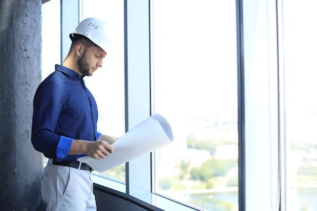 Selbstbewusster junger geschäftsmann im hemd, der blaupause untersucht, während er im büro gegen ein fenster steht.
