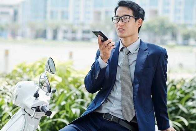 Selbstbewusster junger geschäftsmann in brille, der sprachnachricht für seinen kollegen aufzeichnet