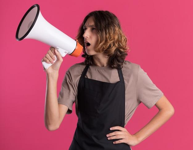 Selbstbewusster junger gutaussehender friseur in uniform, der die hand auf der taille hält und vom lautsprecher spricht, der auf die seite schaut