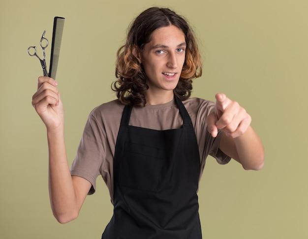 Selbstbewusster junger gutaussehender friseur in uniform mit schere und kamm, der nach vorne auf olivgrüner wand isoliert schaut und zeigt