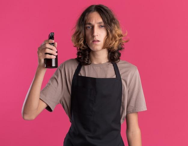 Selbstbewusster junger gutaussehender friseur in uniform mit sprühflasche isoliert auf rosa wand
