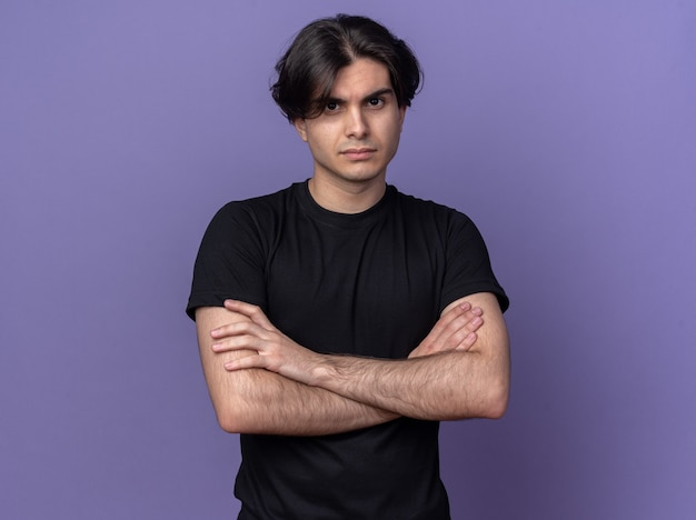 Selbstbewusster junger gutaussehender kerl, der ein schwarzes t-shirt trägt, das die hände isoliert auf lila wand kreuzt