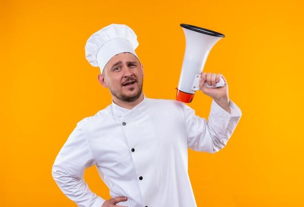 Selbstbewusster junger gutaussehender koch in kochuniform, der einen lautsprecher an einer isolierten orangefarbenen wand hält