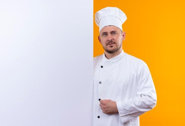 Selbstbewusster junger gutaussehender koch in kochuniform, der hinter weißer wand steht, isoliert auf oranger wand mit kopierraum