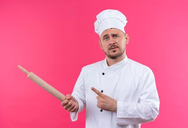 Selbstbewusster junger gutaussehender koch in kochuniform, der nudelholz hält, das auf die seite zeigt, isoliert auf rosa wand