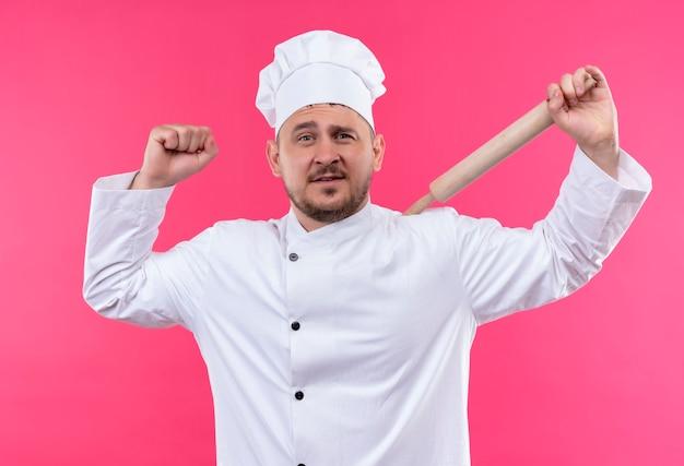 Selbstbewusster junger gutaussehender koch in kochuniform, der nudelholz hält und stark isoliert auf rosa wand gestikuliert