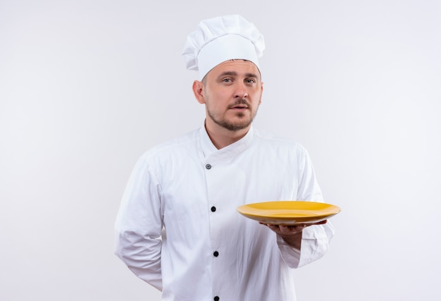 Selbstbewusster junger gutaussehender koch in kochuniform, der teller auf isolierter weißer wand hält