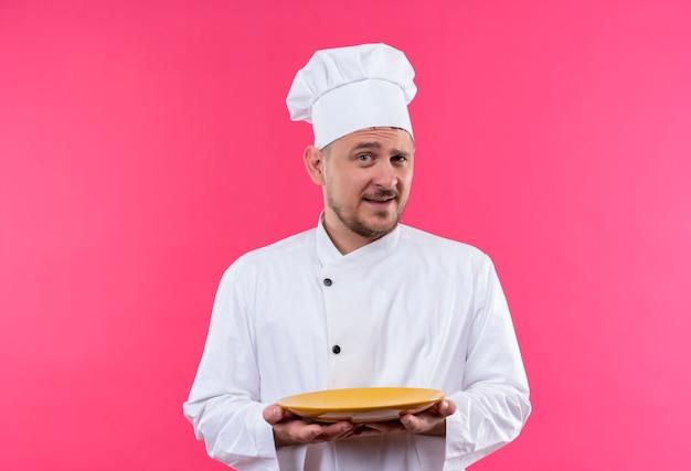 Selbstbewusster junger gutaussehender koch in kochuniform, der teller isoliert auf rosa wand hält