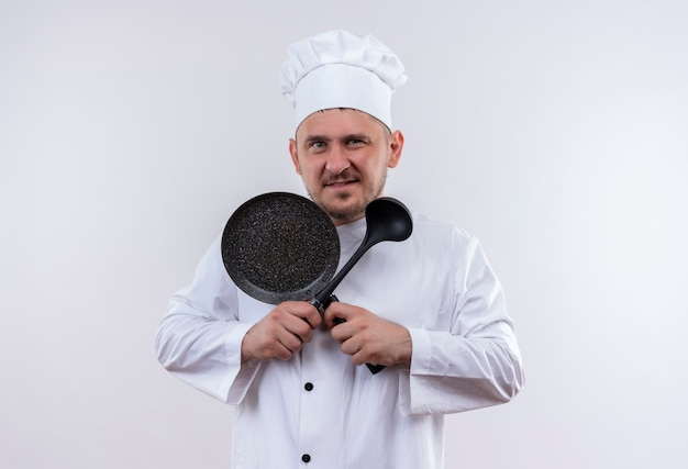 Selbstbewusster junger gutaussehender koch in kochuniform mit bratpfanne und schöpfkelle isoliert auf weißer wand