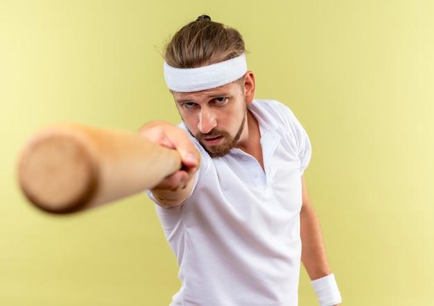 Selbstbewusster junger, gutaussehender, sportlicher mann mit stirnband und armbändern, der baseballschläger in richtung isoliert auf grüner wand ausstreckt