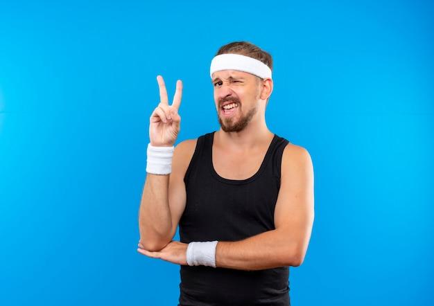 Selbstbewusster junger, gutaussehender, sportlicher mann mit stirnband und armbändern, der ein friedenszeichen macht und die hand unter den ellbogen zwinkert, isoliert auf blauer wand mit kopierraum