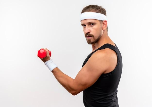 Selbstbewusster junger, gutaussehender, sportlicher mann mit stirnband und armbändern, der eine hantel in der profilansicht isoliert auf weißer wand hält