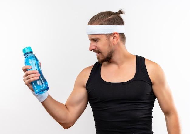 Selbstbewusster junger, gutaussehender, sportlicher mann mit stirnband und armbändern, der eine wasserflasche auf weißer wand hält und betrachtet