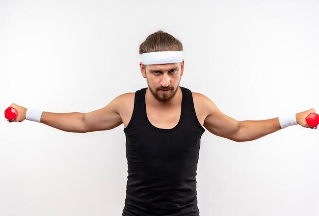 Selbstbewusster junger, gutaussehender, sportlicher mann mit stirnband und armbändern, der hanteln mit offenen armen isoliert auf weißer wand hält und ausstreckt