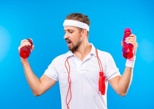 Selbstbewusster junger, gutaussehender, sportlicher mann mit stirnband und armbändern, der wasserflaschen hält, die mit springseil um den hals isoliert auf blauer wand nach unten schauen