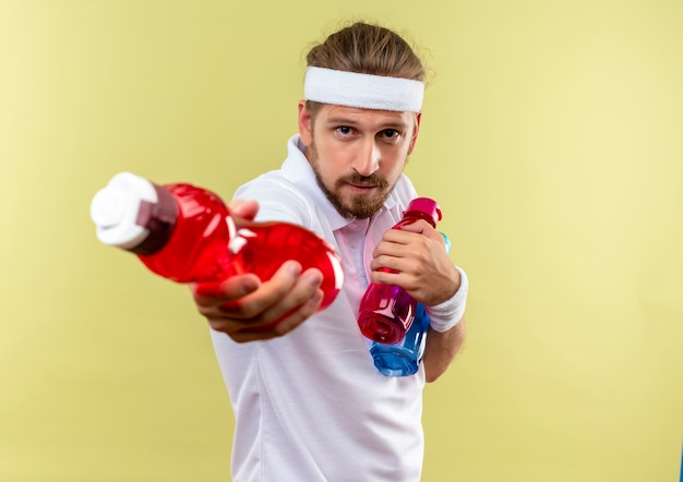 Selbstbewusster junger, gutaussehender, sportlicher mann mit stirnband und armbändern, der wasserflaschen isoliert auf grüner wand mit kopierraum hält und ausstreckt
