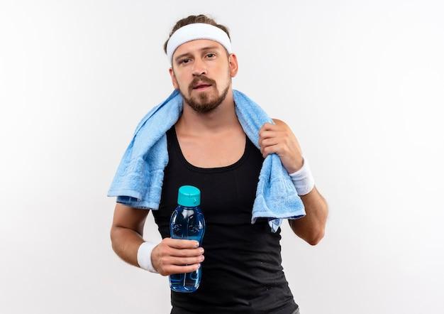 Selbstbewusster junger, gutaussehender, sportlicher mann mit stirnband und armbändern mit handtuch um den hals, das wasserflasche und handtuch isoliert auf weißer wand hält
