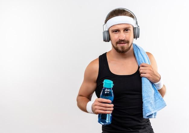 Selbstbewusster junger, gutaussehender, sportlicher mann mit stirnband und armbändern und kopfhörern mit wasserflasche und handtuch auf der schulter isoliert auf weißer wand mit kopierraum