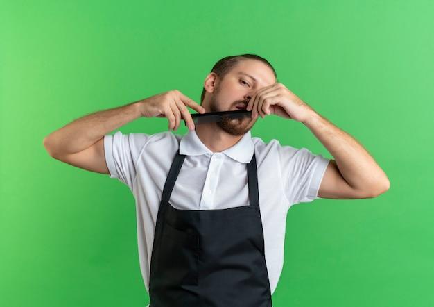Selbstbewusster junger hübscher friseur, der uniform trägt, die seinen bart kämmt, lokalisiert auf grün
