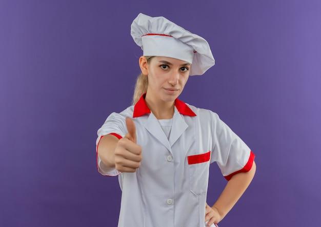 Selbstbewusster junger hübscher koch in kochuniform, der die hand auf die taille legt und den daumen einzeln auf lila wand mit kopienraum zeigt
