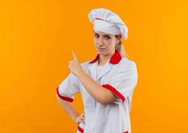 Selbstbewusster junger hübscher koch in kochuniform, der die hand auf die taille legt und nach oben zeigt, isoliert auf oranger wand Kostenlose Fotos