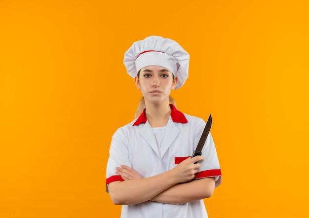 Selbstbewusster junger hübscher koch in kochuniform, der mit geschlossener haltung steht und das messer isoliert auf oranger wand mit kopierraum hält
