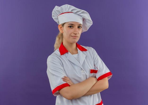 Selbstbewusster junger hübscher koch in kochuniform, der mit geschlossener haltung steht und isoliert auf lila wand mit kopierraum aussieht