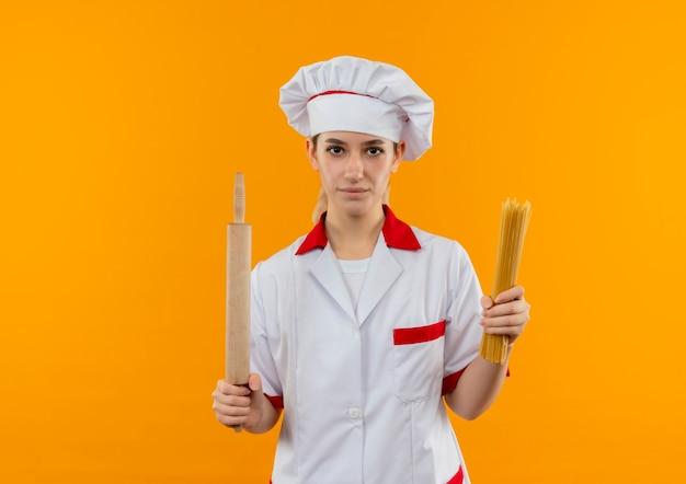 Selbstbewusster junger hübscher koch in kochuniform mit spaghetti-nudeln und nudelholz isoliert auf oranger wand mit kopierraum