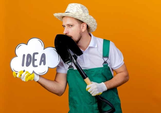 Selbstbewusster junger hübscher slawischer gärtner in der uniform, die hut und gartenhandschuhe trägt, die spaten- und ideenblase halten, die lokal auf orange wand mit kopienraum suchen
