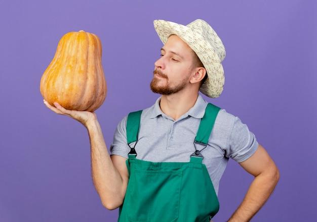 Selbstbewusster junger hübscher slawischer gärtner in der uniform und im hut, die butternusskürbis halten und hand auf taille halten, die auf lila wand lokalisiert hält