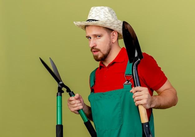 Selbstbewusster junger hübscher slawischer gärtner in der uniform und im hut, die in der profilansicht stehen, die scheren und spaten lokalisiert auf olivgrüner wand hält