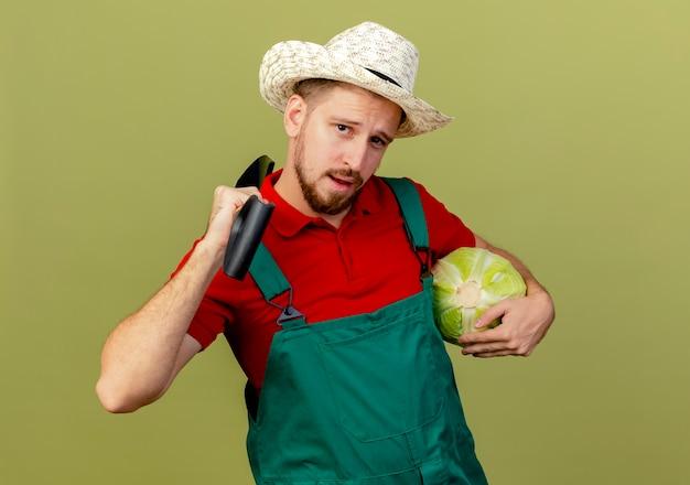Selbstbewusster junger hübscher slawischer gärtner in der uniform und im hut, die kohl und spaten auf schulter lokalisiert auf olivgrüner wand mit kopienraum halten
