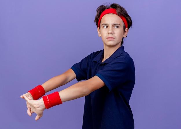 Selbstbewusster junger hübscher sportlicher junge, der stirnband und armbänder trägt und hände streckt
