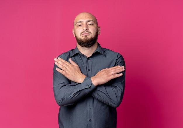 Selbstbewusster junger kahlköpfiger callcenter-mann, der die hände gekreuzt auf purpur mit kopienraum gekreuzt hält