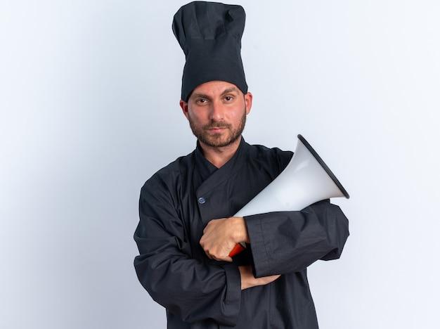 Selbstbewusster junger kaukasischer koch in kochuniform und mütze, der mit geschlossener haltung in die kamera schaut, mit lautsprecher in der hand isoliert auf weißer wand
